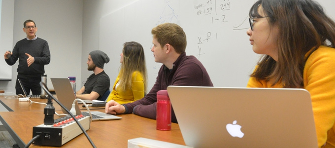 A professor leads his class in discussion