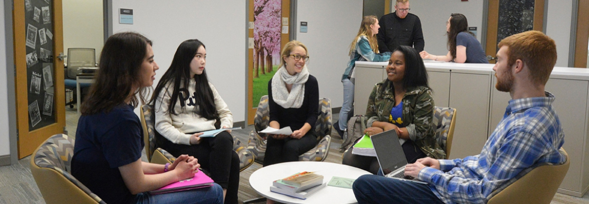 Students have a conversation in a study lounge.